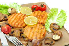 Roasted salmon medallions with mushrooms and vegetables closeup Royalty Free Stock Photo