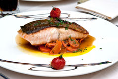 Roasted salmon served with vegetables. In a restaurant Stock Image