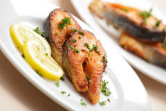 Roasted salmon stakes plated with lemon Royalty Free Stock Photos