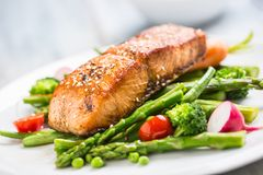 Roasted salmon steak with asparagos broccoli carrot tomatoes rad. Ish green beans and peas. Fish meal with fresh vegetable royalty free stock photo