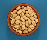 Roasted saltade jordnötter i bunke på blå bakgrund, bästa sikt Arkivfoto