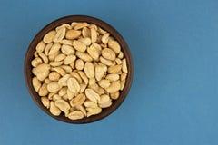 Roasted saltade jordnötter i bunke på blå bakgrund, bästa sikt Royaltyfri Foto