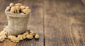 Roasted and salted Almonds with shell. On a vintage background close-up shot Royalty Free Stock Photography