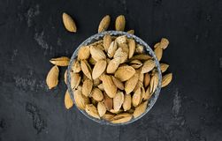Roasted and salted Almonds with shell. On a vintage background close-up shot Stock Photos