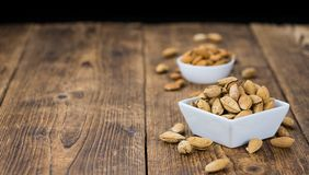 Roasted and salted Almonds with shell. On a vintage background close-up shot Royalty Free Stock Image