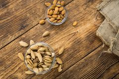 Roasted and salted Almonds with shell. On a vintage background close-up shot Stock Photo