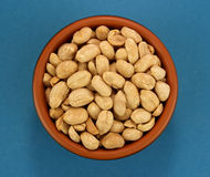 Roasted salted peanuts in bowl  on blue background, top view Stock Photo