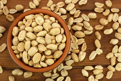 Roasted salted peanuts in bowl on a wooden background Stock Photography