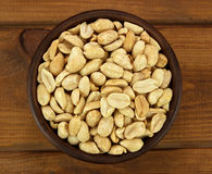 Roasted salted peanuts in bowl on a wooden background Royalty Free Stock Photography