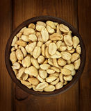 Roasted salted peanuts in bowl on a wooden background Royalty Free Stock Photo