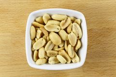Peanuts – Roasted & Salted in a Bowl. Roasted & salted peanuts. The peanut or groundnut, Arachis hypogaea, is a legume classified as a grain legume and an oil Stock Photography
