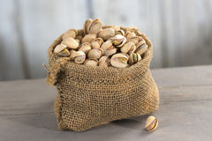 Roasted salty pistachios nuts in burlap bag Stock Photo