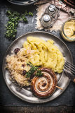 Roasted sausage with Mashed Potatoes and pickled cabbage in metal plate with cutlery served on dark rustic table, top view, close Royalty Free Stock Images