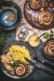 Roasted sausage with Mashed Potatoes and pickled cabbage served on dark rustic table with mustard, top view. Stock Image