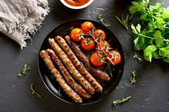 Free Roasted Sausages And Cherry Tomatoes Stock Image - 118499721