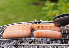Roasted sausages on a barbecue grill outdoors Royalty Free Stock Image