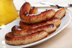 Roasted sausages and beer. Roasted sausages on white plate and beer royalty free stock photography
