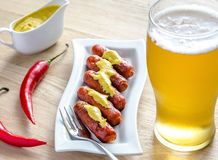 Roasted sausages with glass of beer Stock Photography