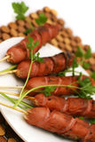 Roasted sausages with parsley. Roasted sausages on white dish with parsley Royalty Free Stock Image