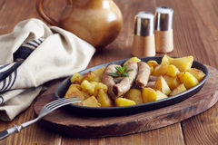 Roasted sausages and potatoes. On a wooden table Royalty Free Stock Photo