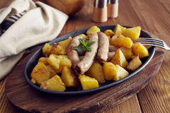 Roasted sausages and potatoes. On a wooden table Stock Photography