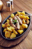 Roasted sausages and potatoes. On a wooden table Stock Photo