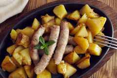 Roasted sausages and potatoes. On a wooden table Stock Photos