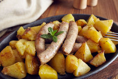 Roasted sausages and potatoes. On a wooden table Stock Images
