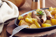 Roasted sausages and potatoes. On a wooden table Royalty Free Stock Photography