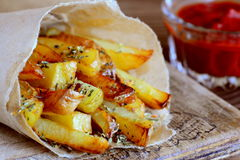 Roasted savoury french fries in paper and on a board, tomato sauce in a glass bowl. Quick potato snack idea Royalty Free Stock Photo
