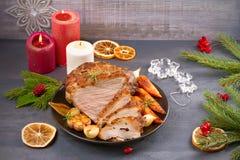 Roasted schnitt Weihnachtsschinken mit Gemüse und festliche Dekoration auf grauem rustikalem Hintergrund lizenzfreies stockbild