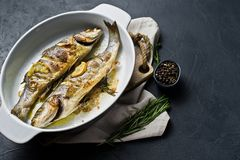 Roasted sea bass in a baking dish. Black background, top view, space for text. royalty free stock image