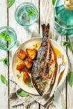 Roasted seabream and potatoes with cherry tomatoes and thyme. On old table royalty free stock photos