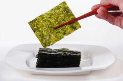Roasted Seaweed. Held with red chopsticks. on white royalty free stock image