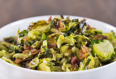 Roasted shaved brussels sprouts with crumbled bacon. A bowl of roasted shaved brussels sprouts cooked with olive oil and crumbled bacon makes a delicious and Royalty Free Stock Photo