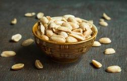 Roasted skalade rimmade jordnötter i lantlig bunke på träbakgrund Royaltyfri Fotografi