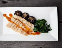Roasted sliced conch with Chinese gravy oyster sauce. Roasted sliced conch with Chinese gravy oyster sauce served with Chinese Hong Kong  kale and black Stock Photography