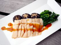 Roasted sliced conch with Chinese gravy oyster sauce. Roasted sliced conch with Chinese gravy oyster sauce served with Chinese Hong Kong  kale and black Royalty Free Stock Images