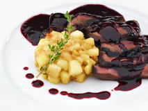 Roasted sliced duck breast meat under wine and berry sauce. Delicious roasted sliced duck breast meat under wine and berry sauce with apples on the white plate royalty free stock photography
