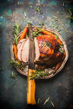 Roasted sliced pork  ham with kitchen knife and roast vegetables on dark rustic background Stock Images