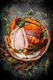 Roasted sliced pork ham and roast vegetables on dark rustic background Royalty Free Stock Photos