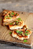 Roasted sliced Turkey fillet with cheese, agaricus and parsley on a cutting board and an old wooden table. Closeup Stock Images