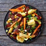 Roasted sliced veggies on a black plate