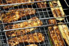 Roasted sliced zucchini on a fire laid out in rows on the grill under burning coals stock photo