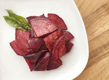 Roasted slices of beetroot. Portion served on a white plate. Wooden background. Top view. Stock Photography