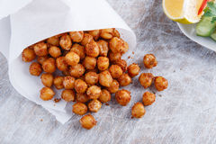 Roasted spicy chickpeas. On rustic background scattered Royalty Free Stock Photos