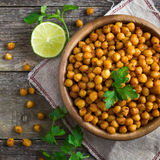 Roasted  spicy chickpeas on rustic background. Top view, square image Royalty Free Stock Image