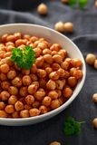 Roasted spicy chickpeas in white bowl. Healthy food royalty free stock image