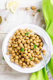 Roasted spicy chickpeas with zaatar or zatar on vintage metall try and wooden background. Top view Royalty Free Stock Images