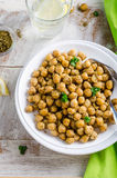 Roasted spicy chickpeas with zaatar or zatar on vintage metall try and wooden background. Top view Stock Photo
